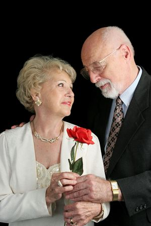 A handsome senior couple in love.  Hes giving her a rose.  A hearing aid is visible in her ear. photo