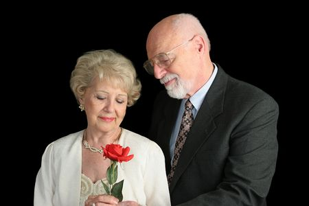 A handsome senior couple (parents of the bride) dressed up for a special occasion.  He has given her a red rose. photo