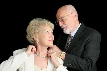 A horizontal view of a senior man fastening his wifes necklace as they prepar for an evening out. photo