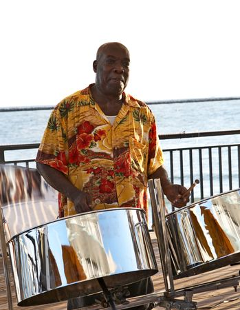 drum: A caribbean musician playing steel drums.