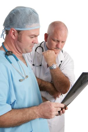 Two concerned doctors reviewing xrays.  Focus on mature doctor in white lab coat. Stock Photo