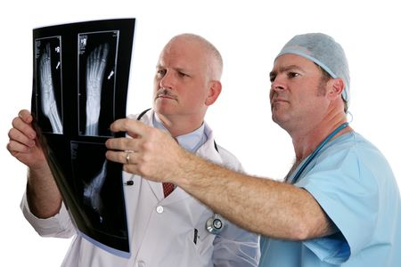 podiatrist: Two doctors examing the xray of a foot.  (focus on young doctor in foreground)
