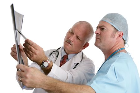 A doctor pointing out something on an xray to his intern. (focus on older doctor) photo