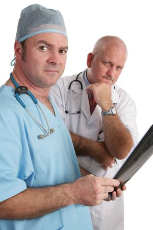 Two doctors examining xrays.  They are looking at the camera with serious expressions. photo