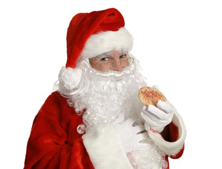 saint nick: Isolated Santa Clause eating a Christmas cookie.   Stock Photo