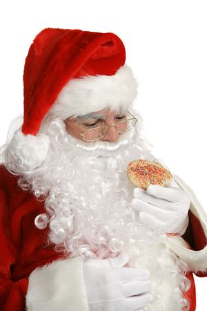 saint nick: Santa considers whether or not to eat a Christmas cookie.  Isolated. Stock Photo