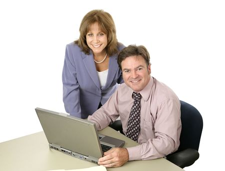 A male female business team working together on the computer.  Both are smiling.  Isolated on white. Imagens