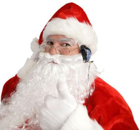 saint nick: Santa Claus listening to headpnones and giving a thumbs up sign.  Isolated on white. Stock Photo