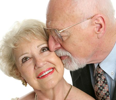 Closeup of a loving senior man gives his beautiful wife a kiss on the cheek. Stock Photo - 551502