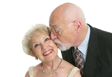 A pretty senior woman giggling as her husband surprises her with a kiss. Stock Photo