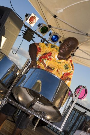 A Caribbean musician jamming on his steel drums. Stock Photo