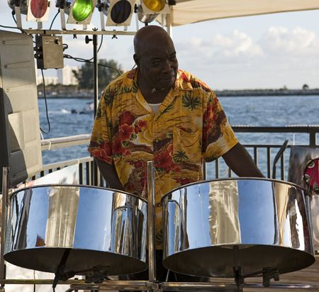 A caribbean musician playing steel drums with the ocean in the background. Stock Photo