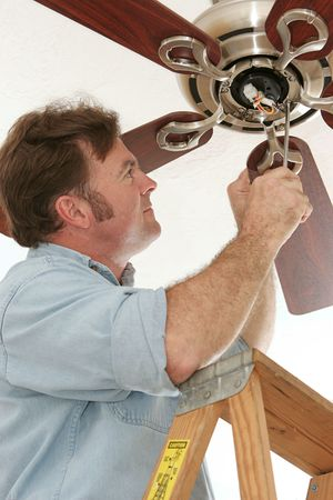 An electrician installing a new ceiling fan.  All work is being performed to code by a licensed master electrician.
