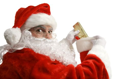 stuffing: Santa is surprised as he is caught in the act of stuffing a childs stocking.  Isolated on white. Stock Photo