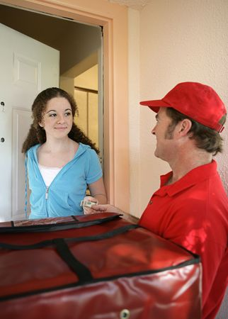 A girl paying the pizza delivery man.