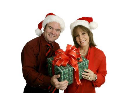 A cute adult couple wearing Santa hats and holding a Christmas gift.  Isolated on white.