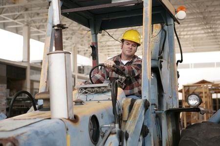 A construction worker driving an earth mover on a construction site. Stock Photo - 580330