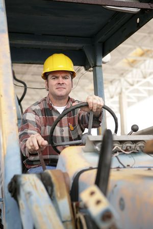 A heavy equipment operator driving a backhoe. Stock Photo - 580331