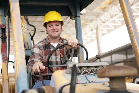 建設現場でブルドーザーを運転ハンサムな建設労働者。 写真素材