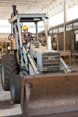 A man on a construction site driving a backhoe loader. photo