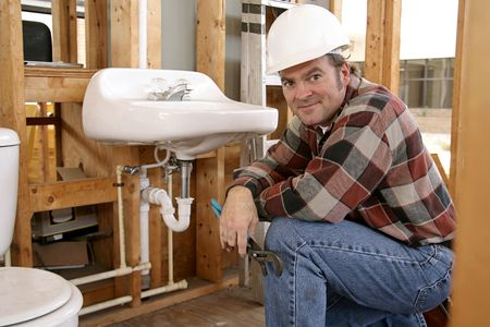 A construction plumber installing bathroom fixtures in a home under construction. photo