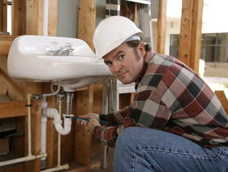 A plumber installing fixtures in a construction site. photo