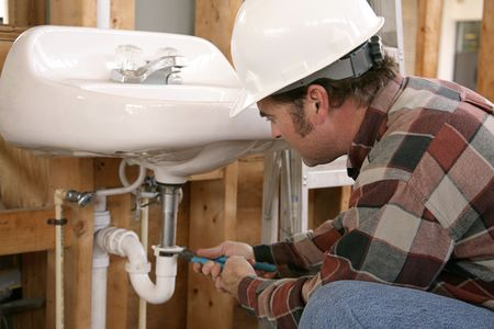 A plumber in new home construction installing bathroom fixtures.  Focus on plumbers face.