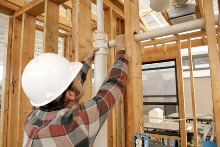home builder: A construction worker connecting plumbing pipe in an unfinished wall. Focus is on the connecting pipes.