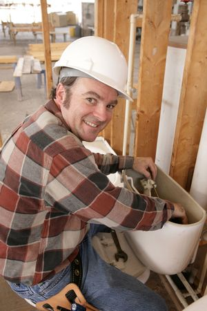 A plumber repairing a toilet on a construction site. photo