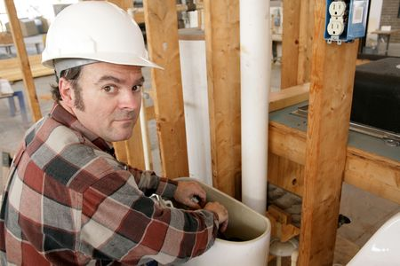 A construction plumber fixing a toilet on new building construction. photo