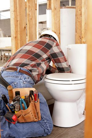 A plumber installing fixtures in new construction.  Focus on his tool pouch. photo
