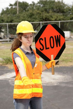 A female construction road crew member holding a slow sign for traffic. photo