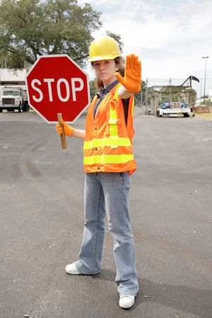 A female construction worker holding a stop sign.  Full body view. Stock Photo - 620261