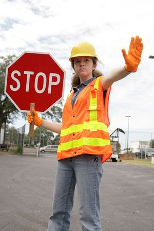 A female construction worker stopping traffic. Reklamní fotografie - 620260