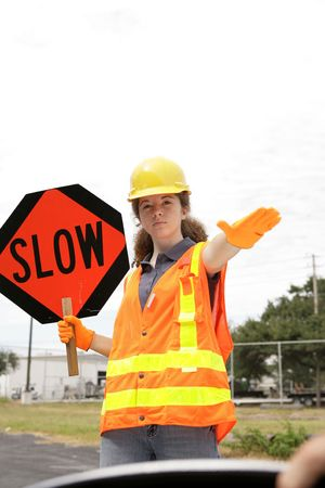 A road crew member holding a sign & telling a driver to slow down. Room for text Stock Photo - 620259