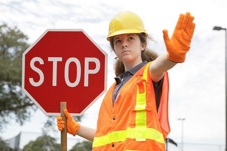 female construction worker: A female construction worker holding a stop sign.