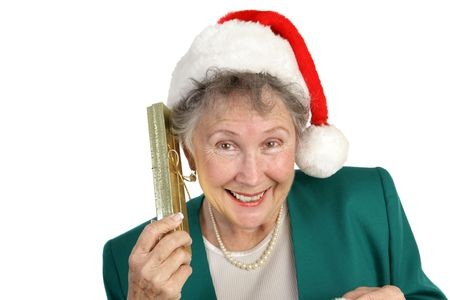 A pretty senior woman in a Santa Hat shaking a gift box to hear what is inside.  Isolated on white. photo