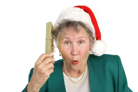 An attractive senior woman with a surprised expression shaking a Christmas gift.  Isolated on white. Stock Photo - 641328