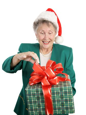 A senior woman anticipating opening a big Christmas gift.  Isolated on white. photo