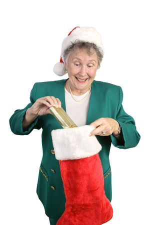 An excited senior woman opening her Christmas stocking.  Isolated on white. photo