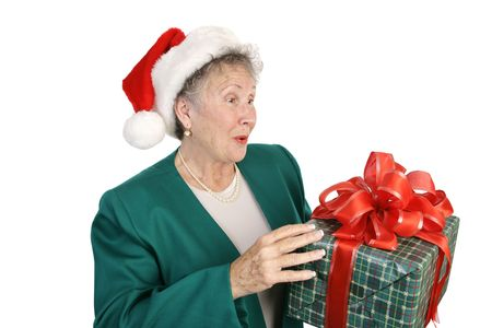 A pretty senior lady holding a surprise Christmas gift.  Isoalted on white. Stock Photo - 641245
