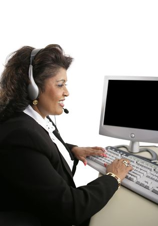 An Indian customer service representative at the computer wearing a headset.  Isolated on white. Stock Photo - 656825