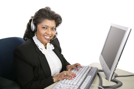 A friendly Indian woman at the computer offering technical support.  Isolated on white. Stock Photo - 656850
