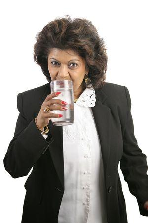 sorbo: Una hermosa india de negocios tomando un sorbo de agua de un vaso. Aislado en blanco.