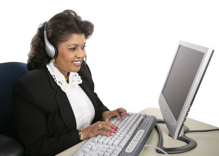 emerging markets: An attractive Indian technical support specialist sitting at the computer with a headset on.  Isolated on white.
