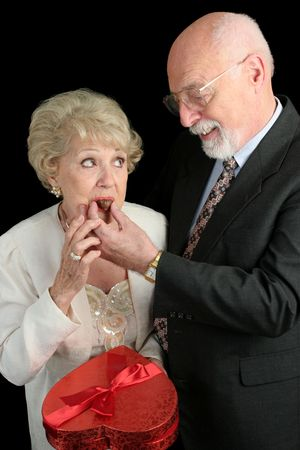 A humorous picture of a husband feeding his wife Valentine candy.  She doesnt look too sure about it.  Black background