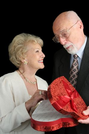 A handsome senior man giving a valentine gift to his beautiful wife.  Black background. photo