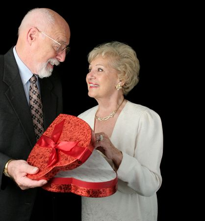 A romantic senior couple on Valentines Day.  Black background. photo