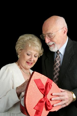 A handsome senior man giving a box of Valentine chocolate to his beautiful wife.  Black background. Stock Photo - 656838