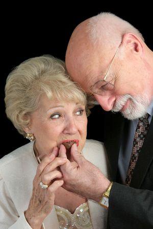 A handsome senior man romantically feeding chocolates to his beautiful wife.  Black background. photo